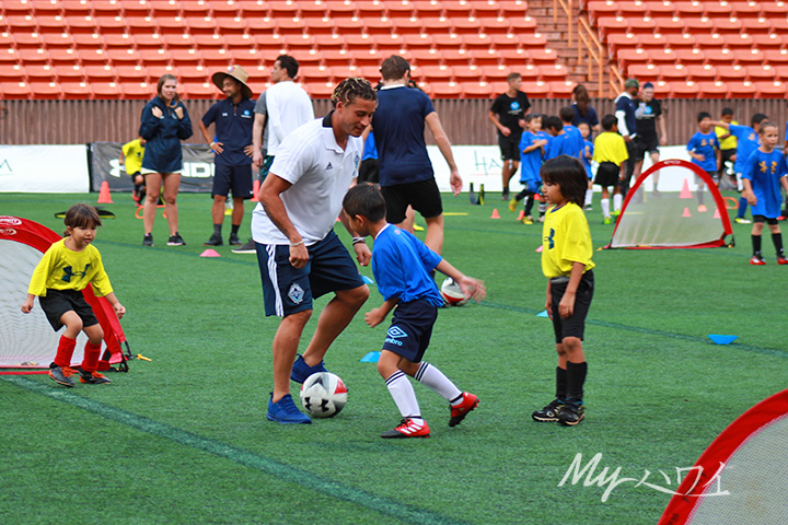 MLS player playing soccer with Children